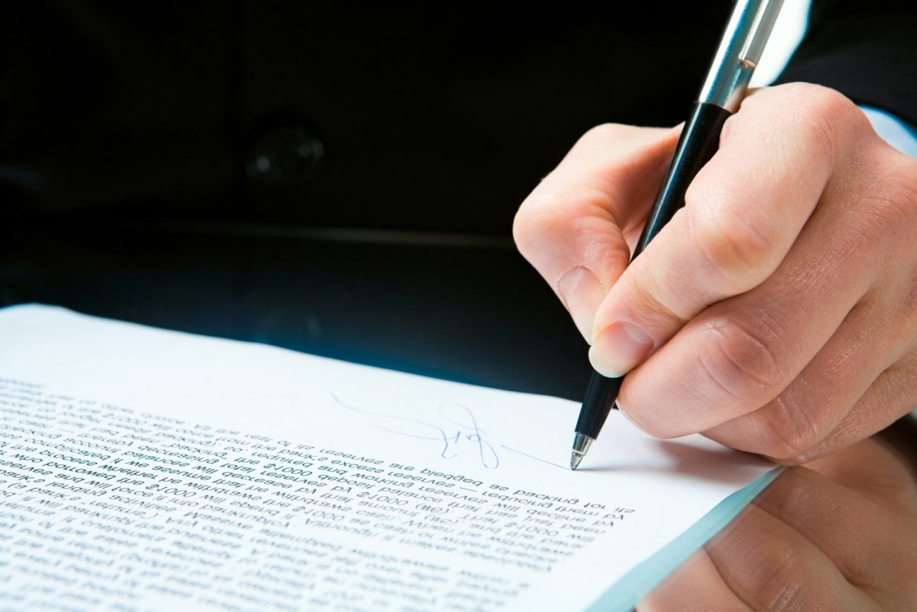 Conceptual image of human hand signing a document